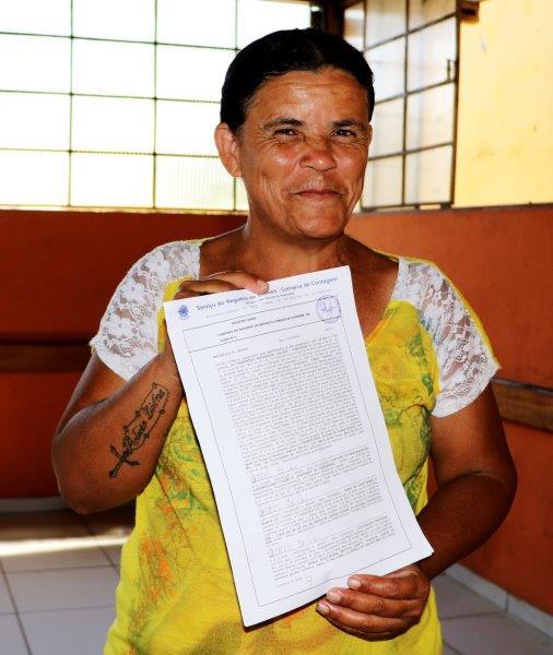 A moradora Maria Auxiliadora Batista Duarte exibe o registro de imóvel